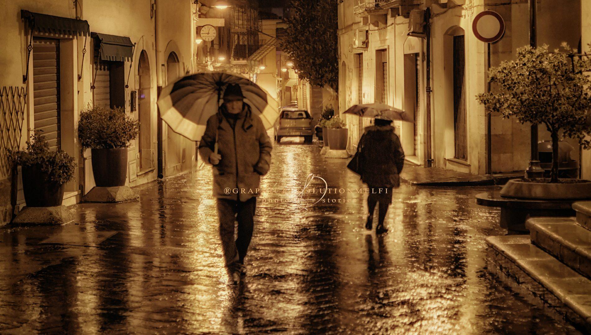 Passanti | Melfi sotto la pioggia in Via Ronca Battista